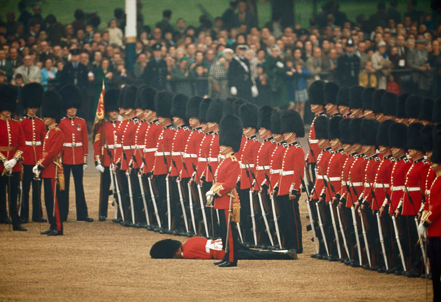 Irish Guards remain at attention after one guardsman faints in London, England, June 1966.