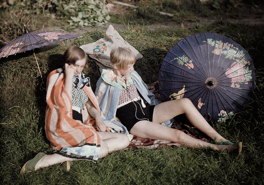 Two young girls enjoy the sun relaxing in their suits and wraps in England, September 1929.